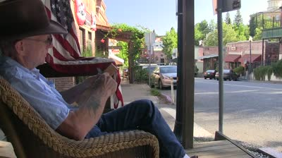 stock footage old small town america man whittling sitting on rocking chair american flag on sidewalk and old